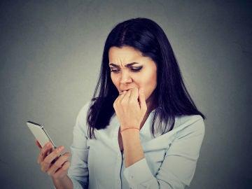 Mujer inquieta al revisar el móvil