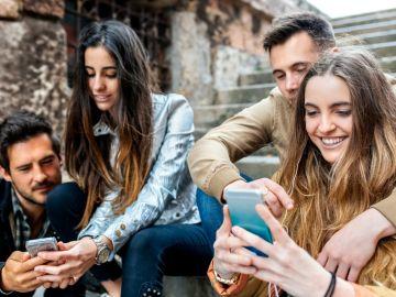 Grupo de chicos y chicas mirando el móvil