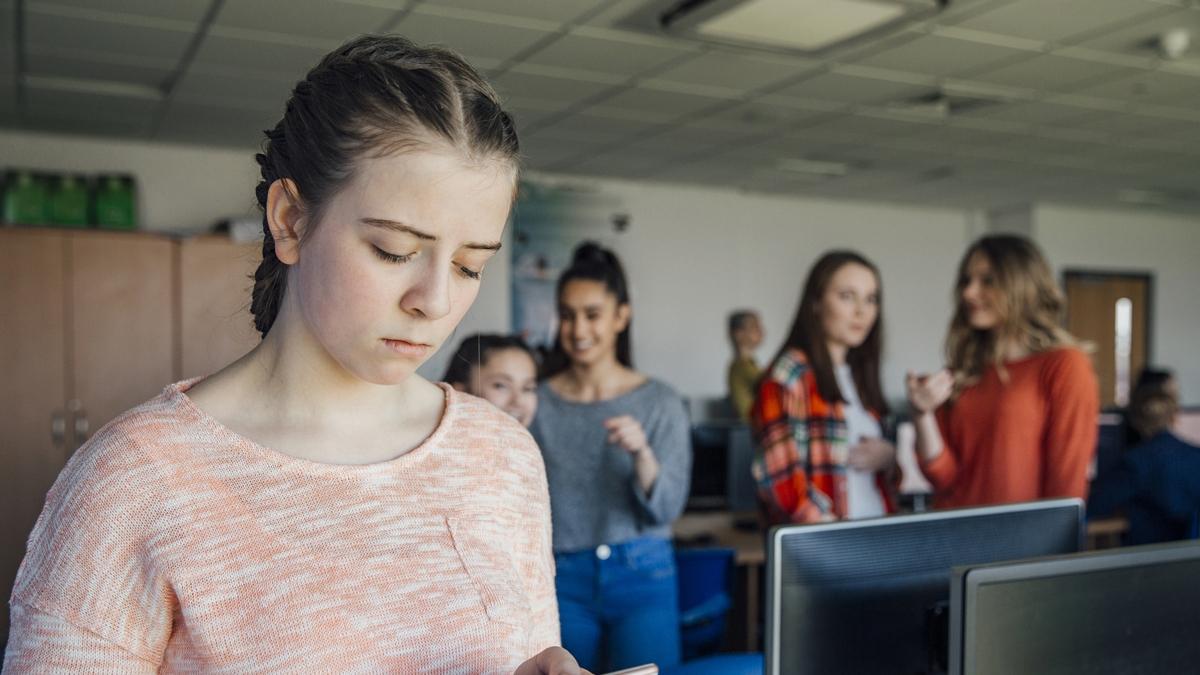 Chica mirando el móvil mientras el resto la miran a ella