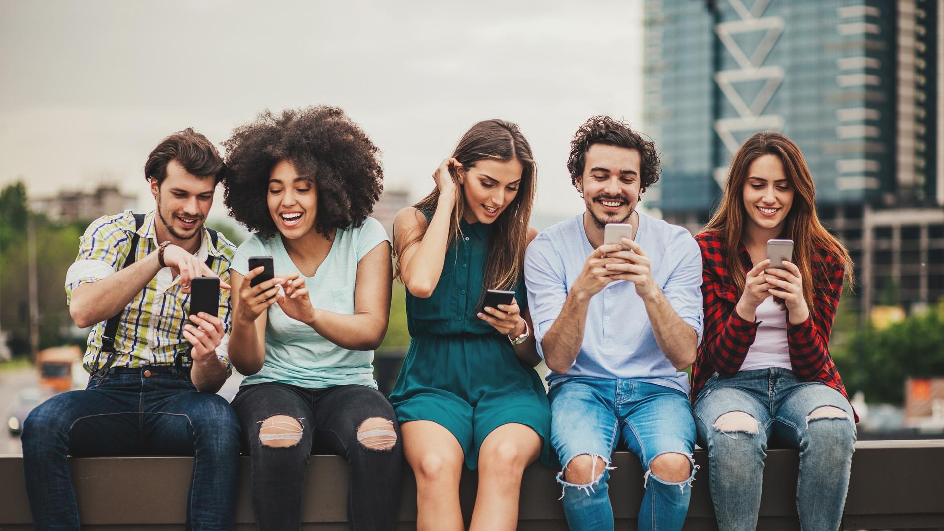Grupo de amigos analizando sus móviles