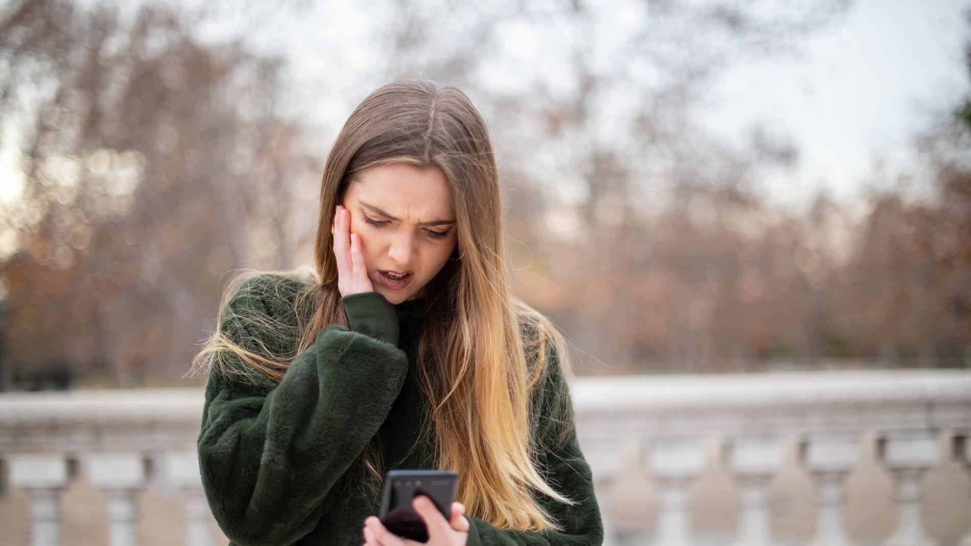 Chica extrañada con lo que lee en su móvil.