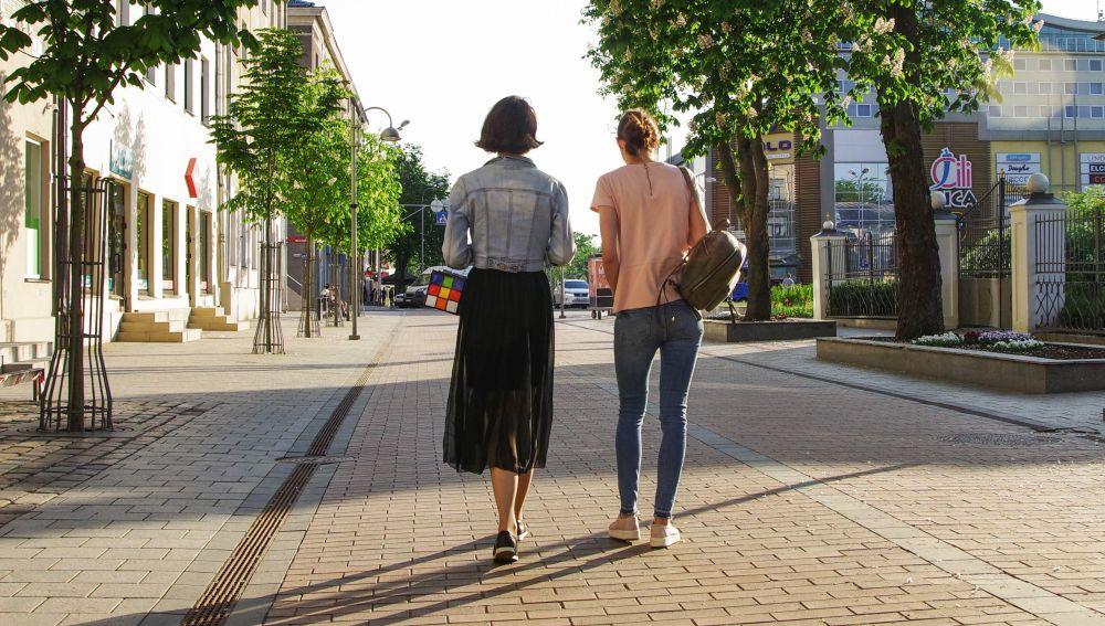 Dos chicas caminando solas por la calle de día