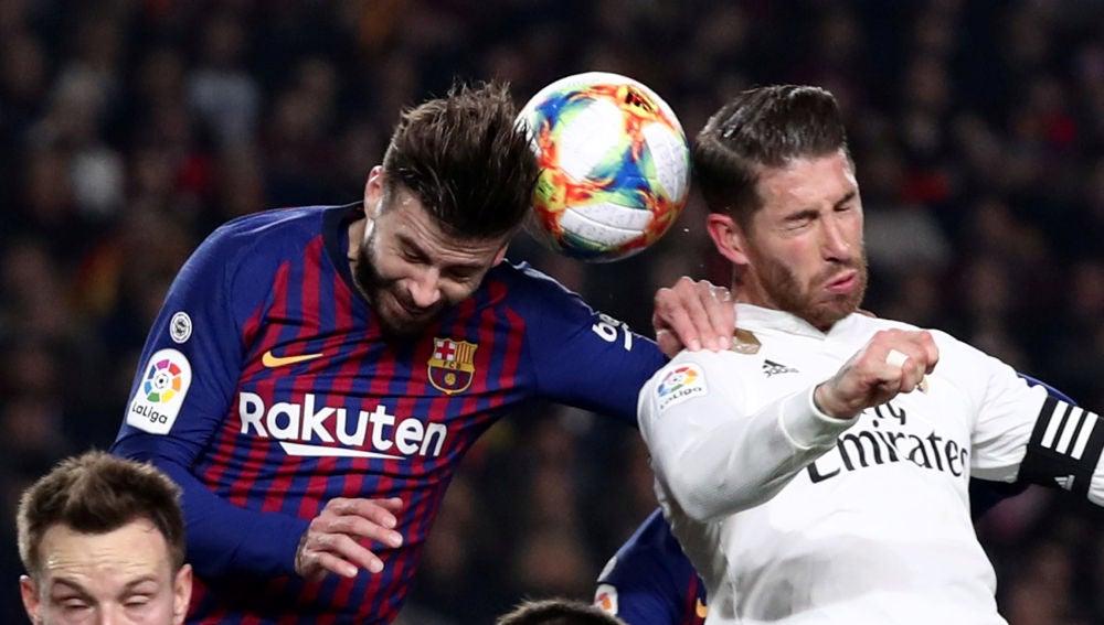 Piqué y Sergio Ramos pugnan por un balón aéreo