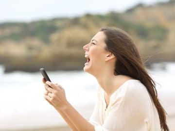 Joven enfadada que mira su teléfono móvil