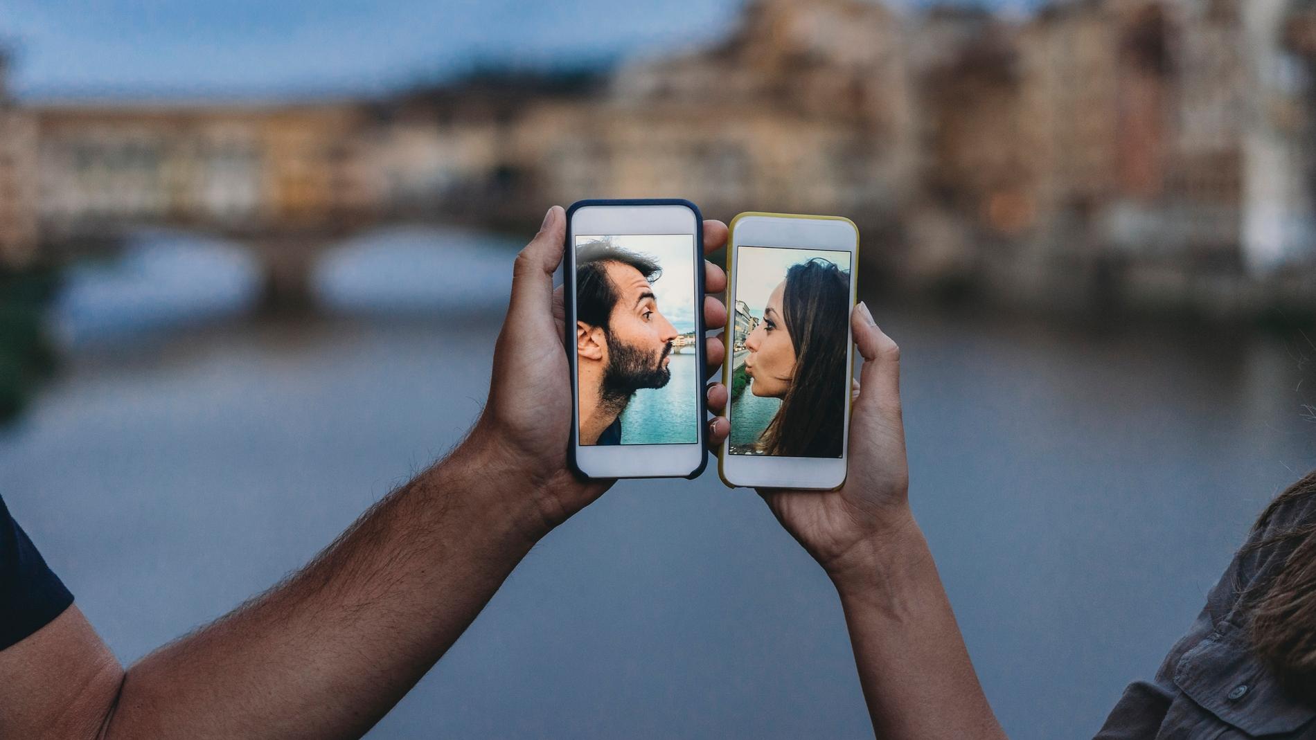 Pareja besándose a través de un móvil.