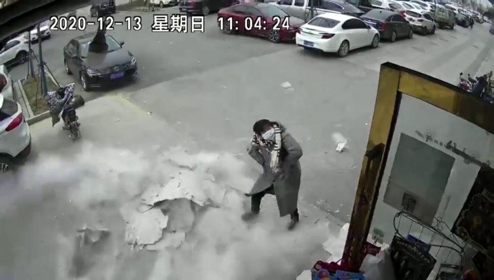 Una mujer esquiva por poco una pared que casi le cae encima